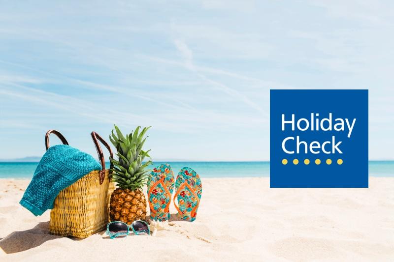 Logo HolidayCheck na tle plaży i morza