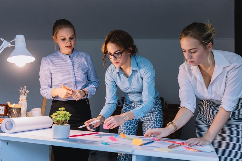 trzy dziewczyny pracujące nad projektem rozłożonym na biurku przy zapalonej lampce biurowej