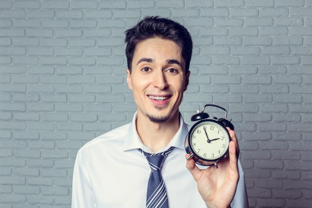 Uśmiechnięty mężczyzna pokazujący stary zegarek z budzikiem na tle ceglanej ściany