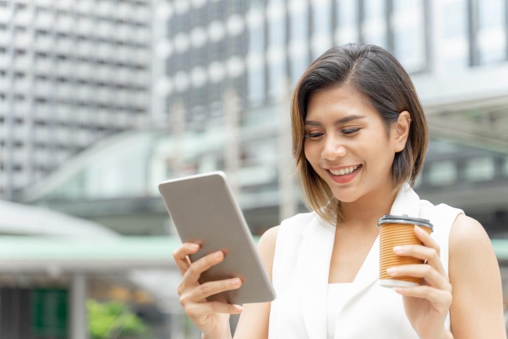 Uśmiechanie dziewczyna spoglądająca w telefon z kawa w drugiej dłoni, na tle biurowców.