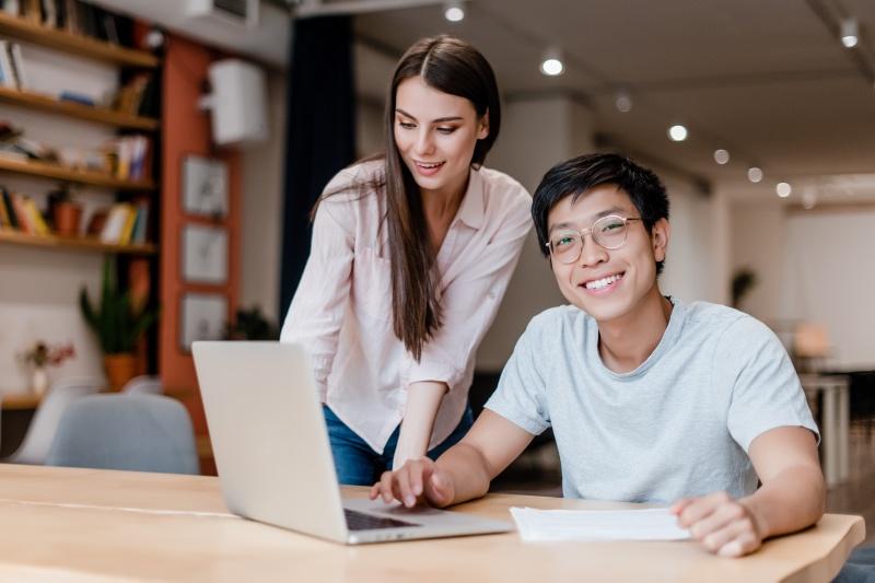 dwójka młodych osób pracująca na laptopie w biurze