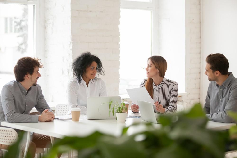 cztery osoby siedzące przy duży biurku omawiajace projekt
