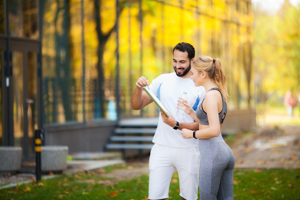 system motywacji pracowników - para młodych ludzi w stroju sportowym w parku czytająca plan treningowy