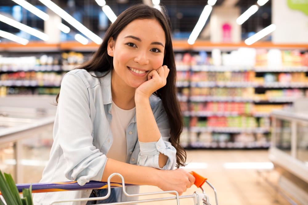 młoda uśmiechnięta dziewczyna na zakupach w markecie opierająca się o wózek zakupowy