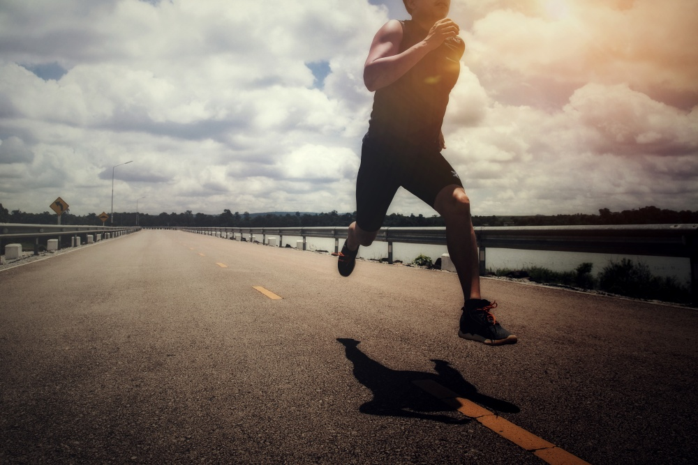 biegnący mężczyzna środkiem pustej drog