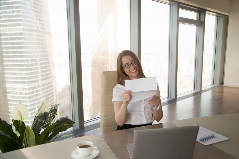Uśmiechnięta młoda dziewczyna, czytająca dokument siedząc w pomieszczeniu biurowym przy biurku
