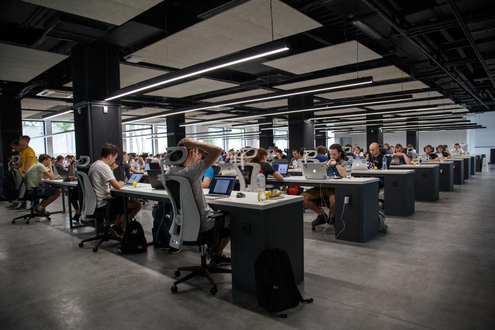 Bardzo duza grupa osób pracująca w open space