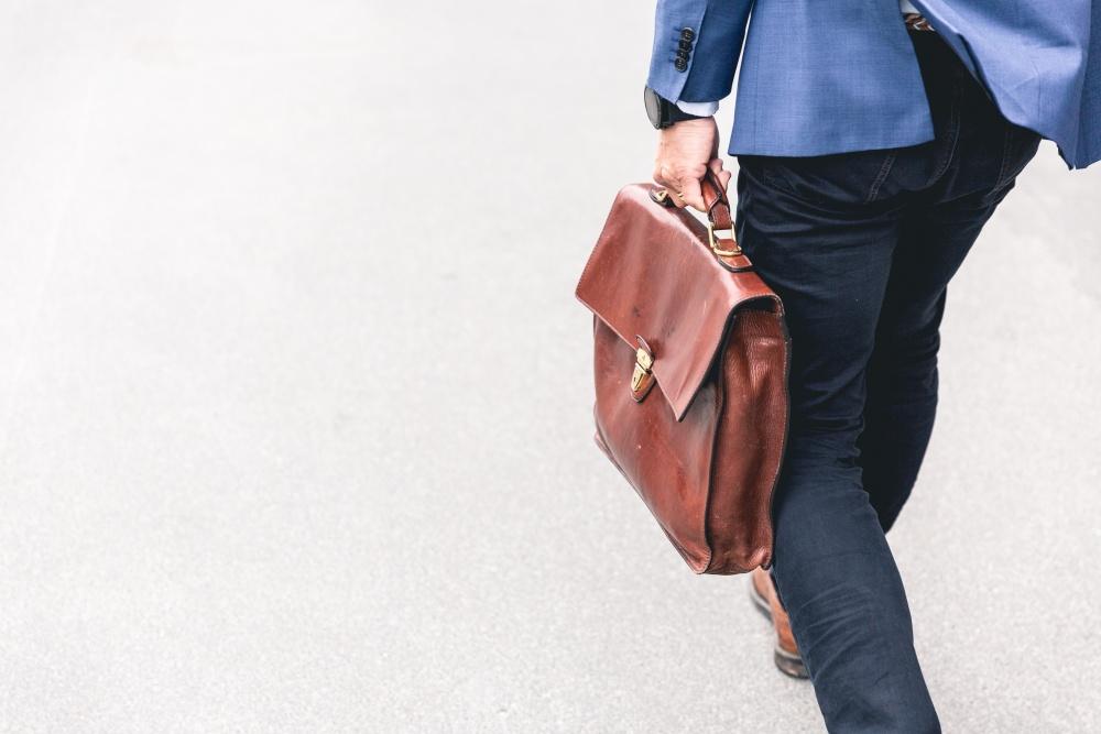 skórzana torba trzymana przez mężczyznę idącego do pracy