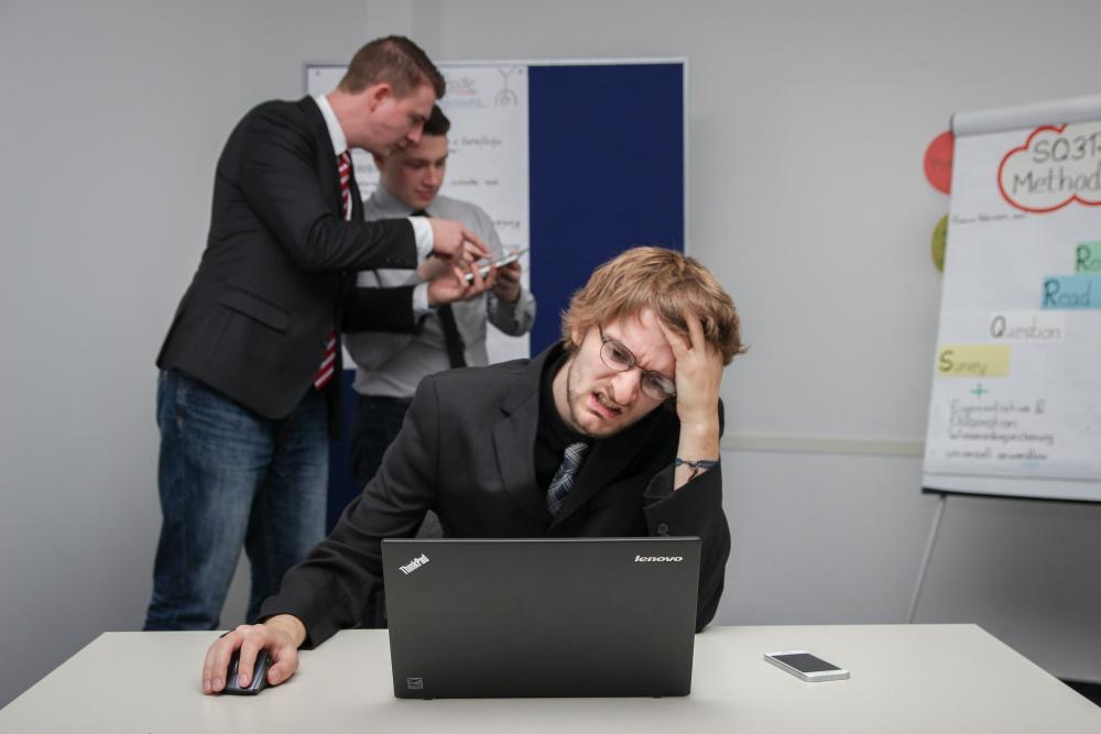 sfrustrowany mężczyzna siedzący przed laptopem w pracy