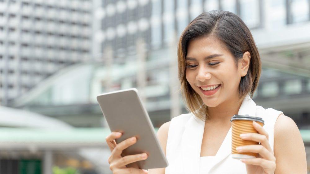 Uśmiechanie dziewczyna spoglądająca w telefon z kawa w drugiej dłoni, na tle biurowców. wellbeing pracowników